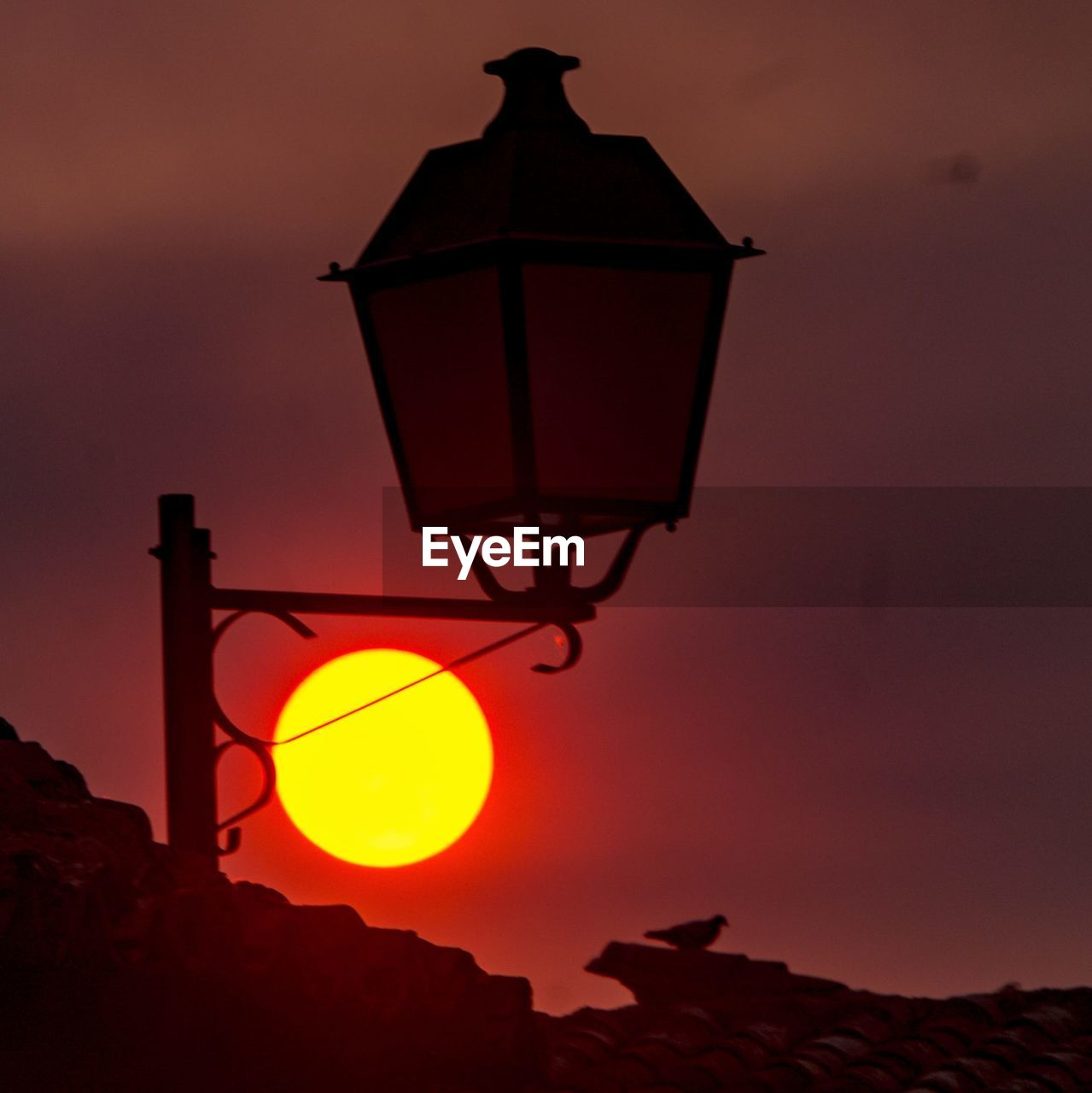 LOW ANGLE VIEW OF LANTERN AGAINST SKY DURING SUNSET