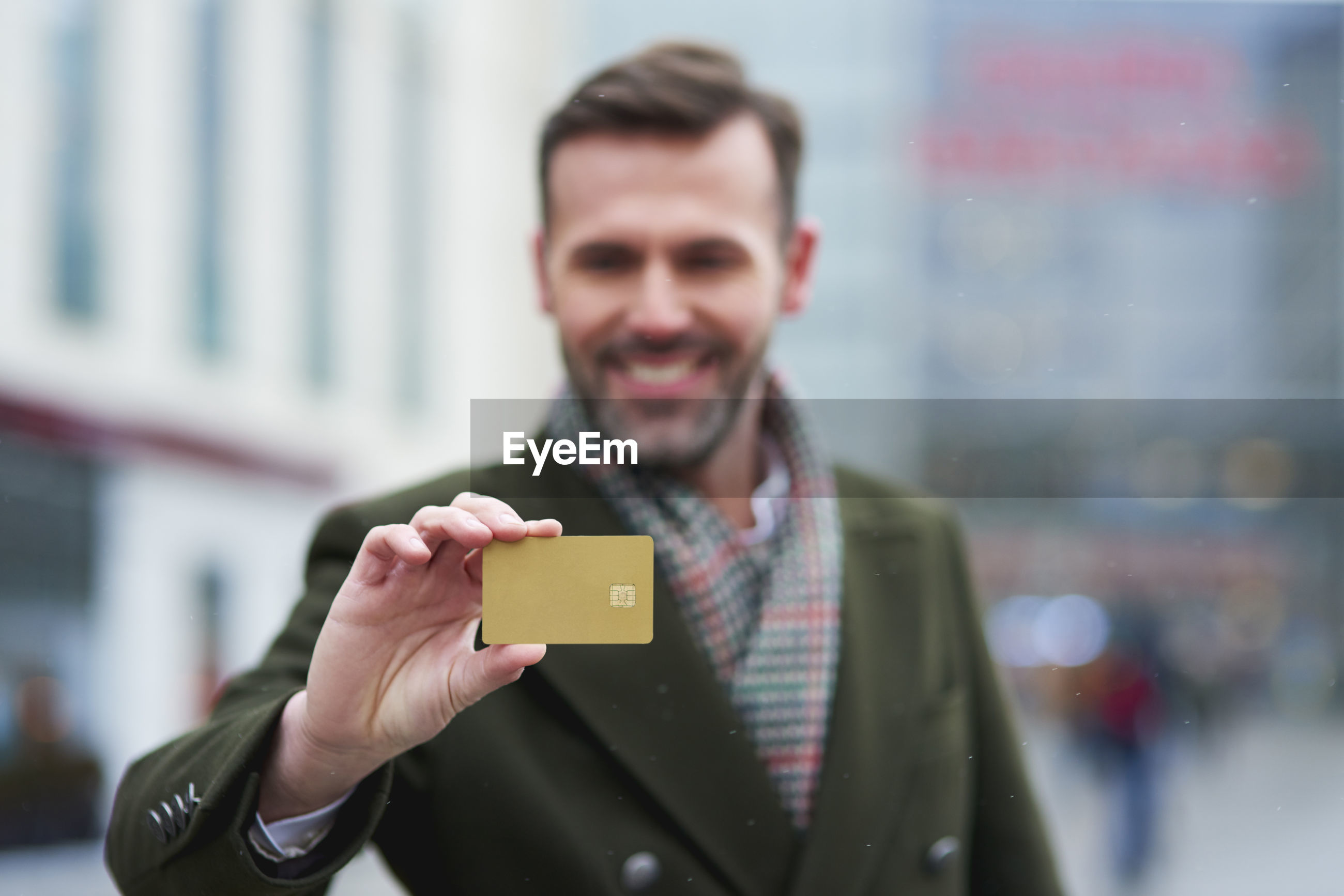 Man holding credit card while standing in city during winter