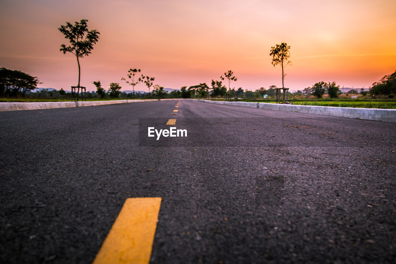 SURFACE LEVEL OF ROAD AGAINST SUNSET SKY