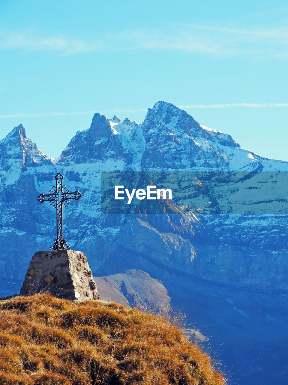 Cross Shape On Hill Against Snowcapped Mountains
