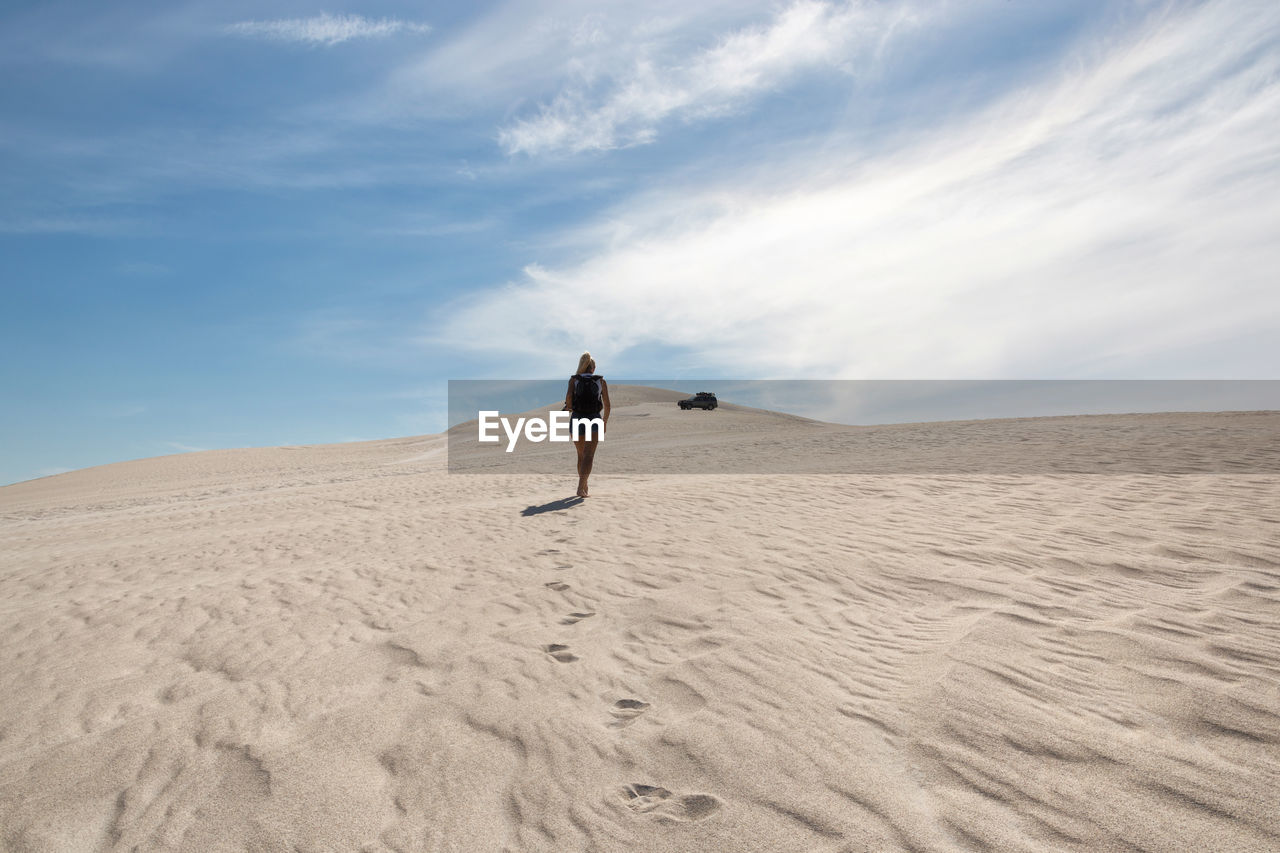 Rear view of woman walking on sand dune against sky