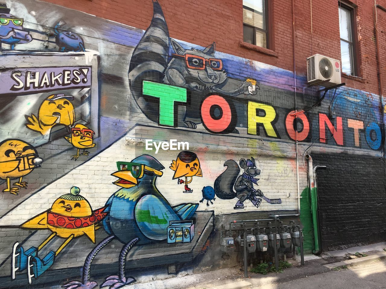 graffiti, architecture, human representation, building exterior, built structure, representation, art and craft, text, creativity, communication, city, multi colored, street art, western script, male likeness, no people, wall - building feature, wall, day, female likeness, brick, outdoors, mural