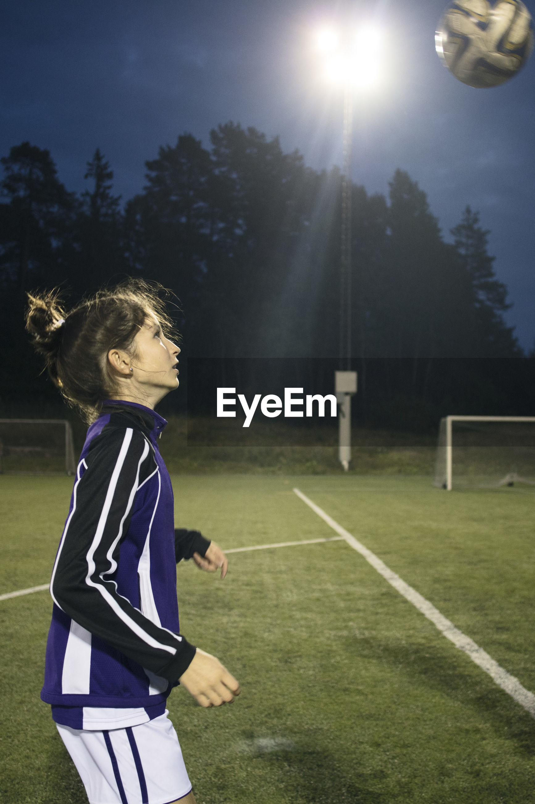 SIDE VIEW OF GIRL PLAYING SOCCER BALL