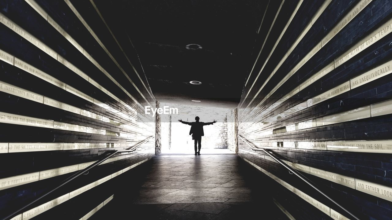 Silhouette Man Standing With Arms Outstretched In Tunnel