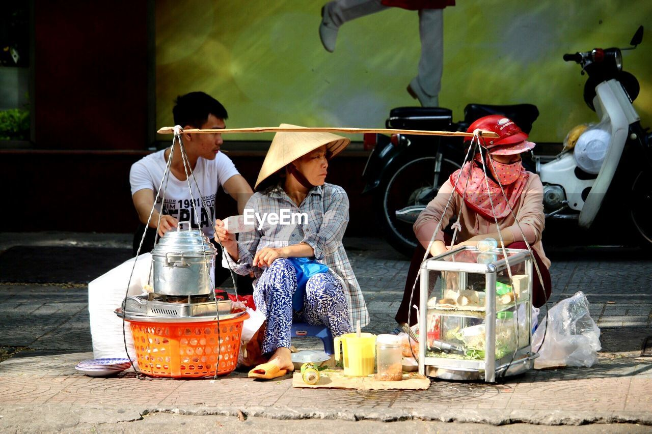 real people, container, women, sitting, men, day, people, adult, incidental people, two people, occupation, food and drink, preparing food, plastic, market, lifestyles, clothing, nature, selling