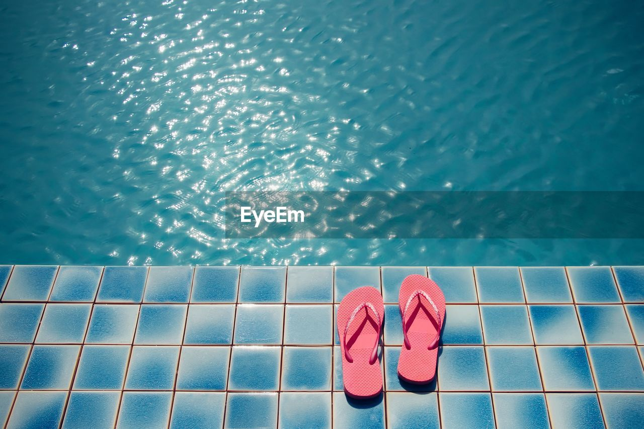 water, swimming pool, pool, one person, body part, low section, human body part, blue, shoe, leisure activity, human leg, real people, poolside, lifestyles, red, nature, tile, day, human foot, nail, flooring, slipper, tiled floor, at the edge of