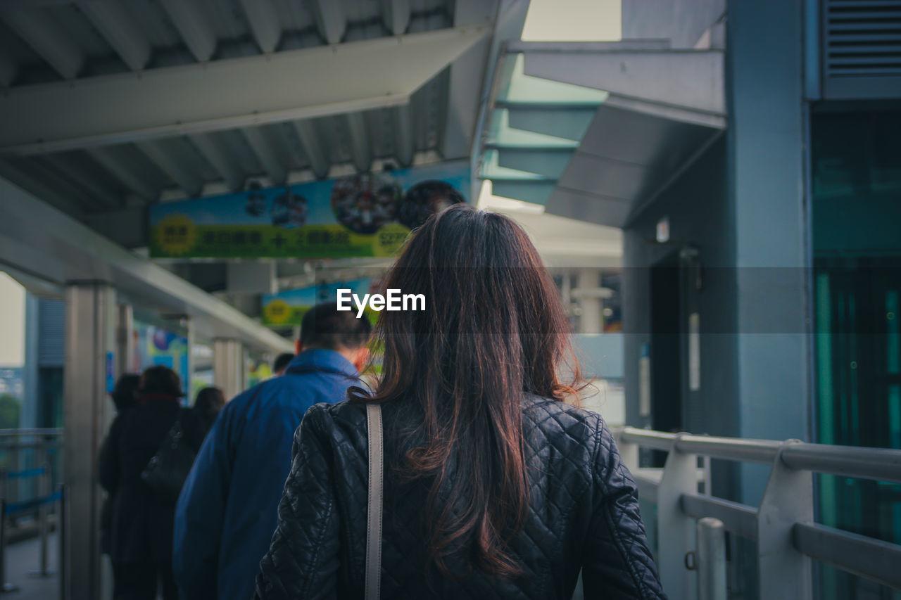 Rear view of woman walking by railing at subway station