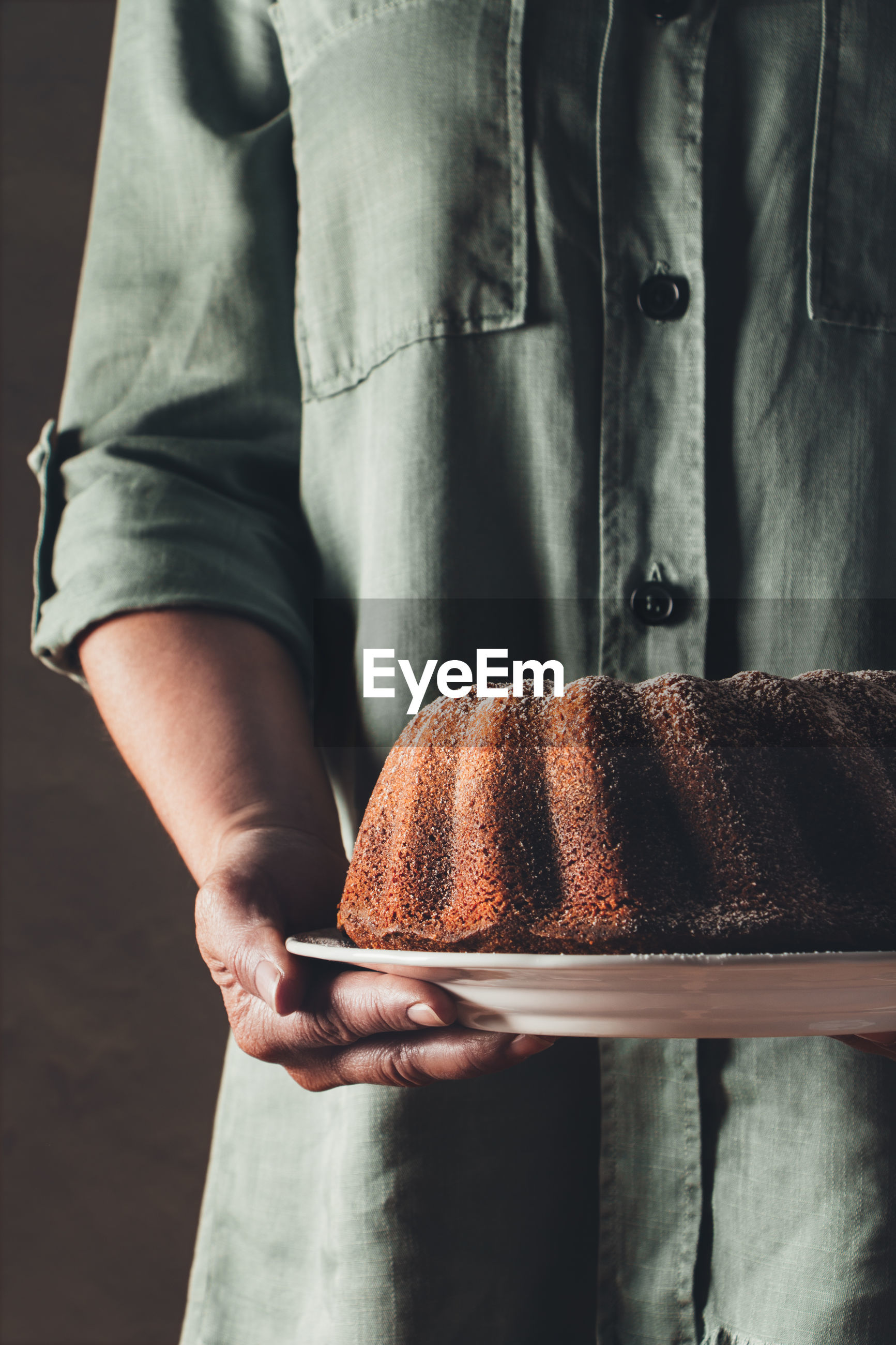 Midsection of man holding bundt cake in plate