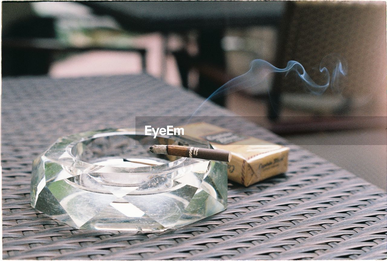 focus on foreground, table, no people, close-up, container, still life, seat, ashtray, cigarette, day, outdoors, business, selective focus, cafe, smoking issues, bad habit, paper, social issues