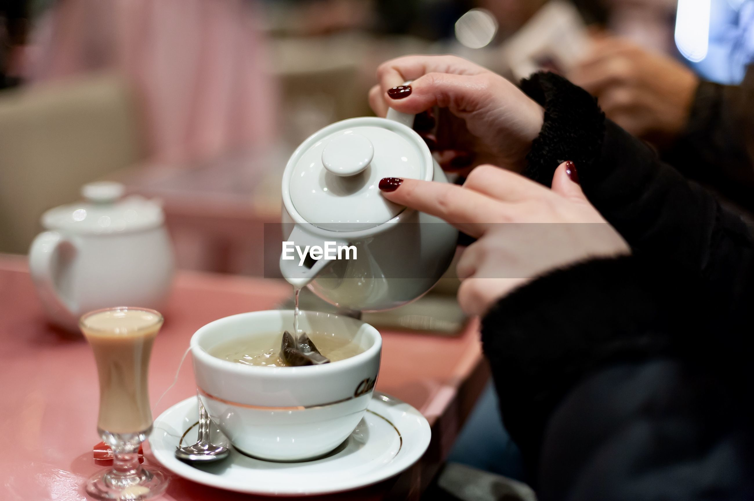 MIDSECTION OF MAN HOLDING COFFEE CUP AND TABLE