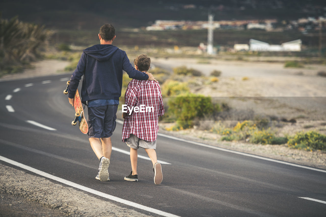 Rear View Of Father And Son Walking On Road In City