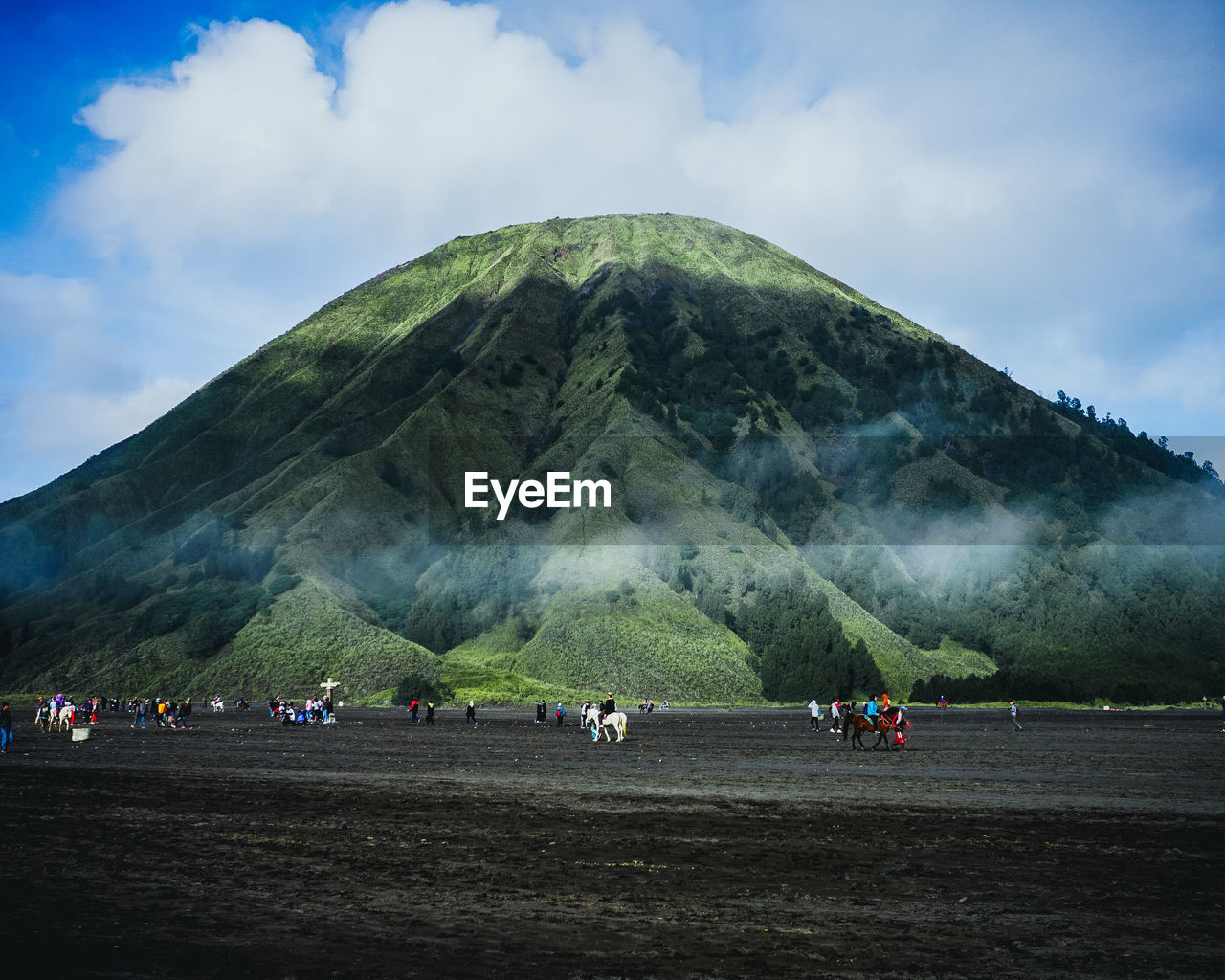 Distant View Of Tourists On Field Against Volcano