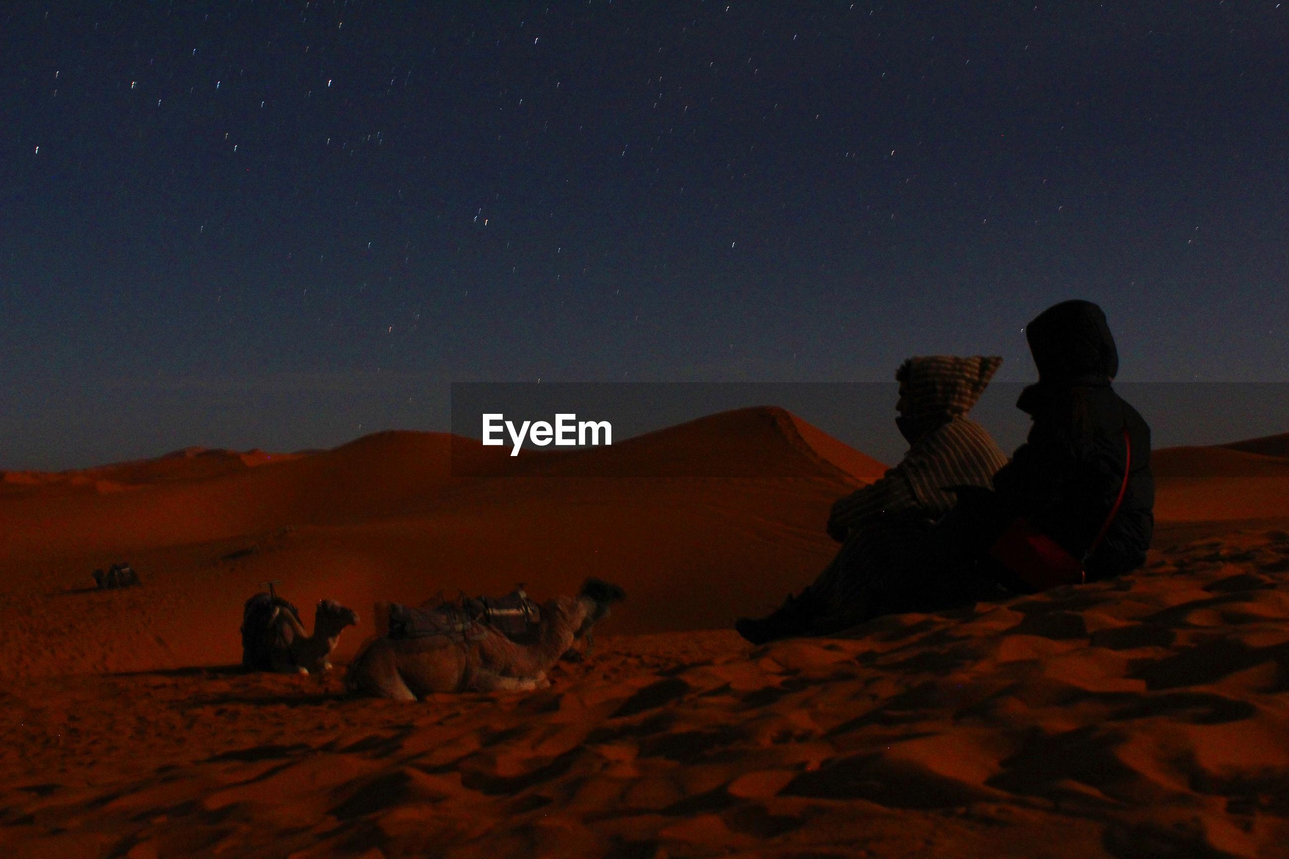 REAR VIEW OF MEN SITTING ON DESERT AGAINST SKY