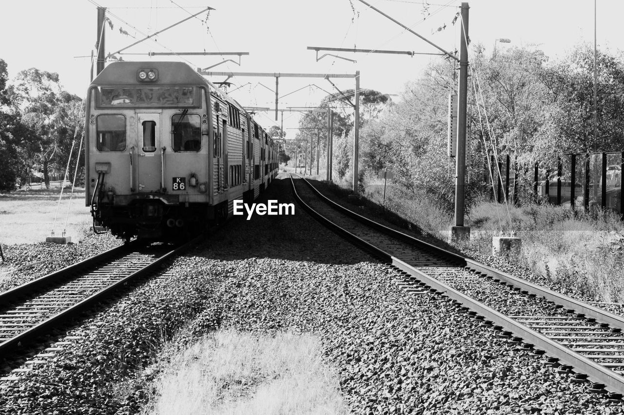 rail transportation, transportation, track, mode of transportation, railroad track, train, train - vehicle, public transportation, tree, nature, plant, day, sky, travel, no people, passenger train, motion, land vehicle, on the move, outdoors, power supply, arrival
