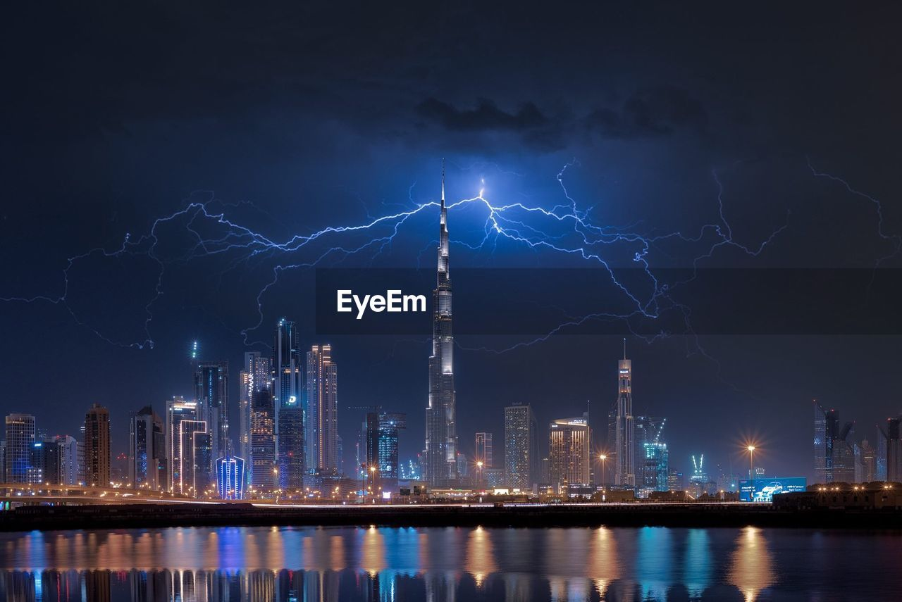 building exterior, night, architecture, illuminated, city, built structure, lightning, sky, water, power in nature, cloud - sky, building, nature, no people, thunderstorm, tower, storm, power, waterfront, tall - high, skyscraper, office building exterior, cityscape, outdoors, modern, electricity