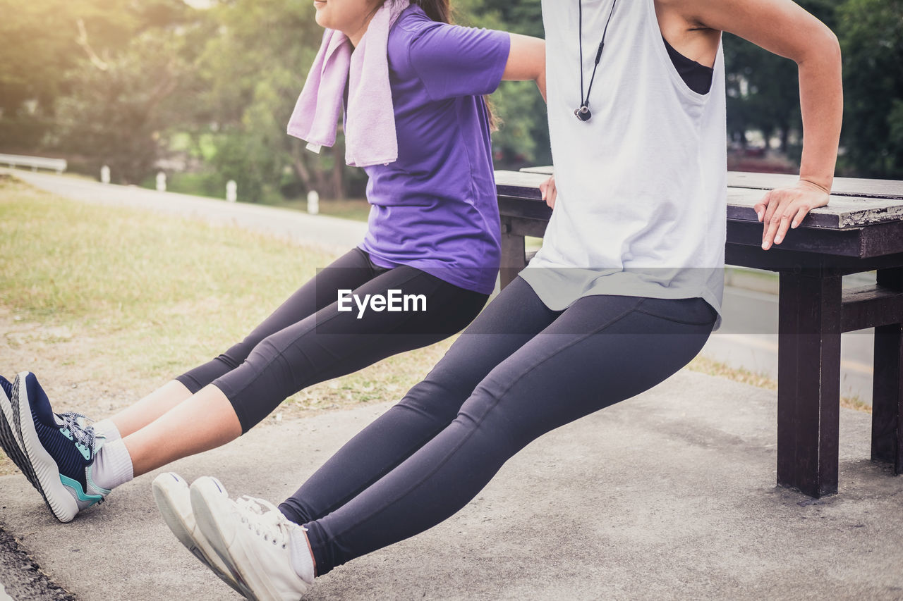 Low section of friends exercising at park
