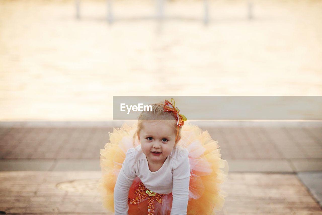 Portrait Of Cute Girl In Tutu Crouching On Footpath