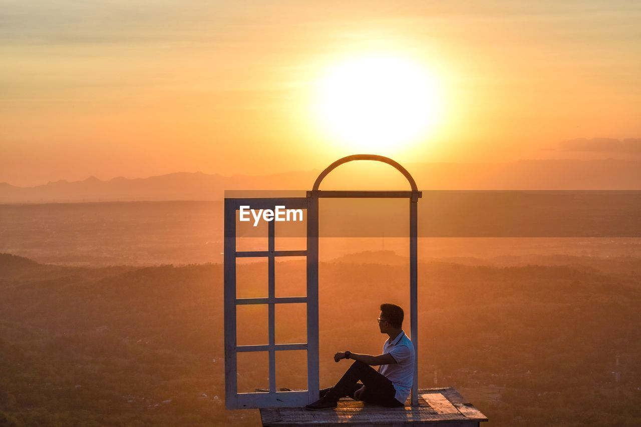 Man Looking At View While Sitting With Door Against Sky During Sunset