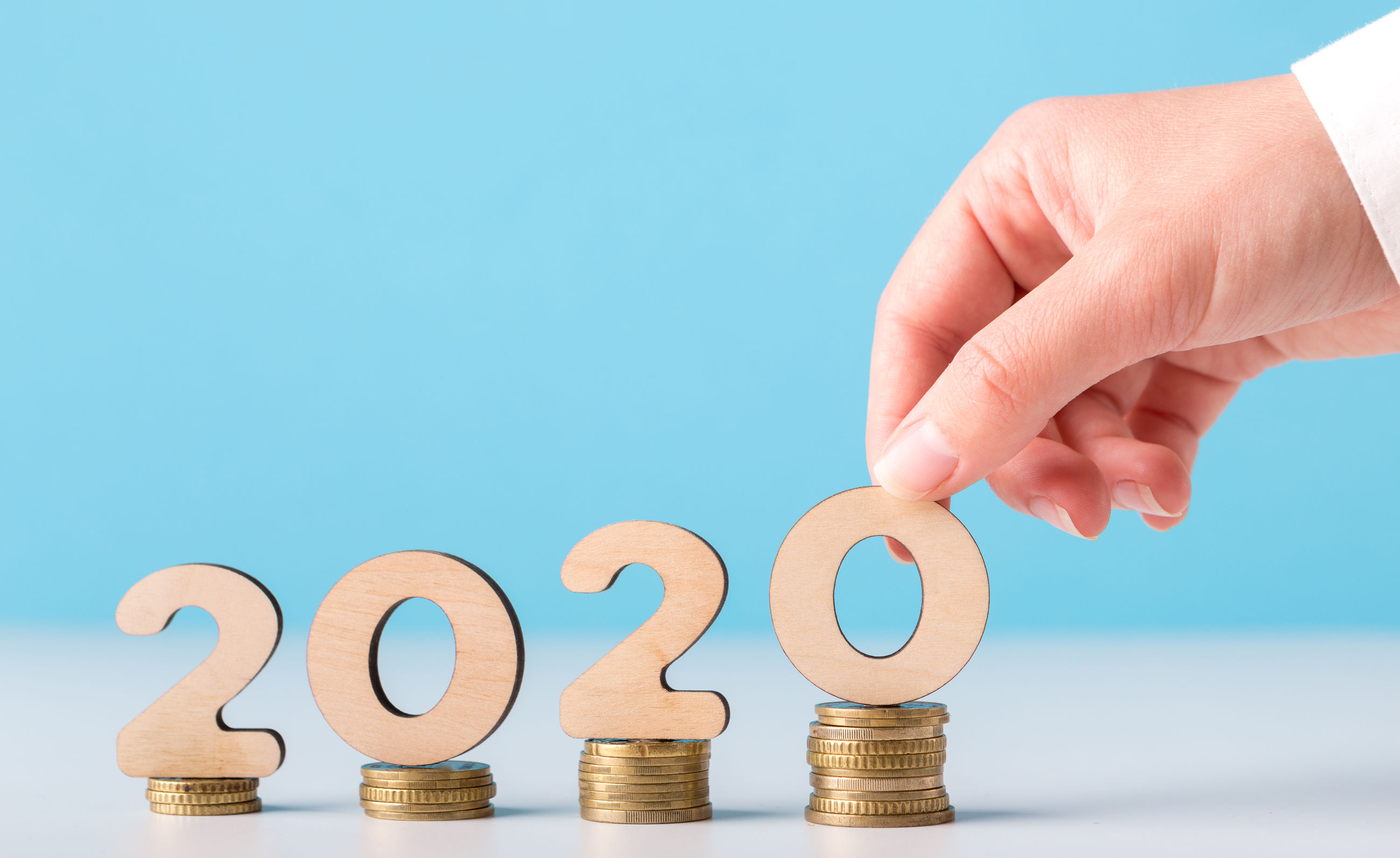 Cropped hand holding 2020 numbers on coins against blue background