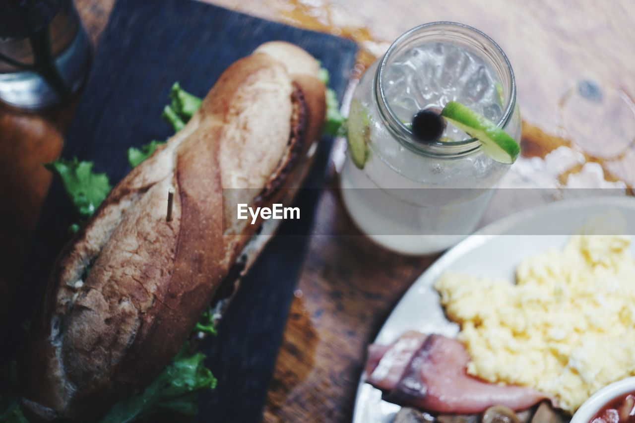 food and drink, food, freshness, healthy eating, meal, bread, ready-to-eat, wellbeing, close-up, table, indoors, sandwich, drink, high angle view, meat, serving size, household equipment, refreshment, still life, glass, hand, breakfast, snack, temptation