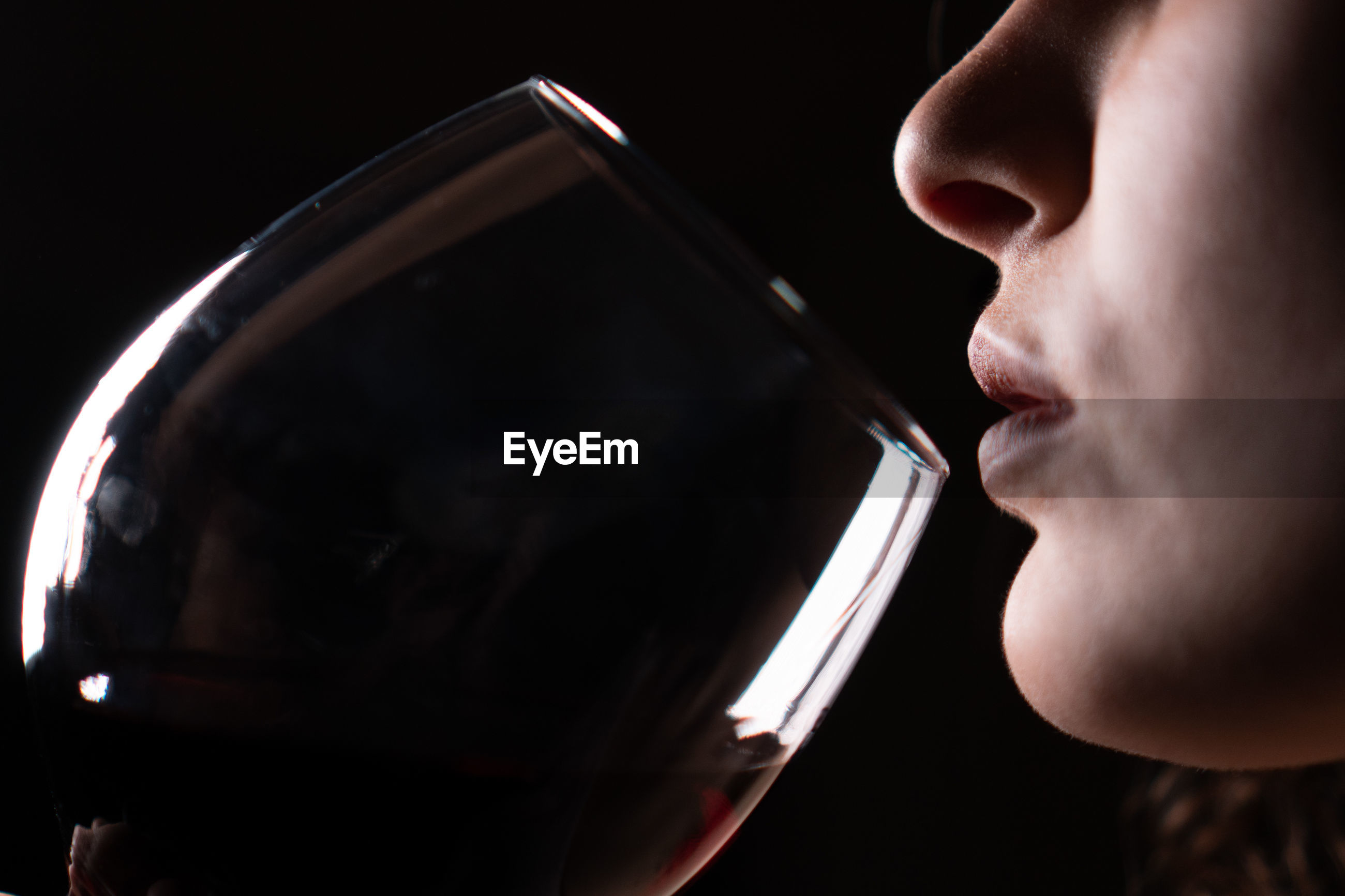 CLOSE-UP PORTRAIT OF A WOMAN DRINKING FROM GLASS