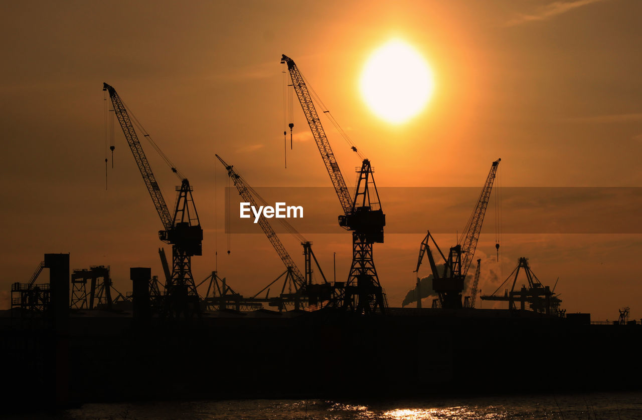 Low angle view of crane against sunset
