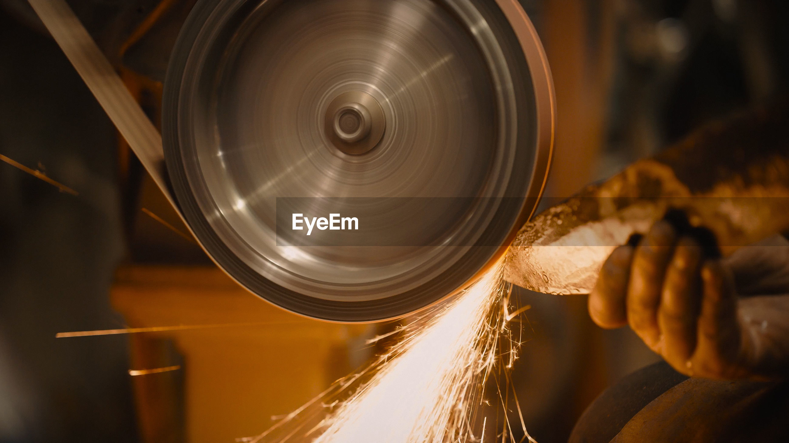 Cropped hand grinding metal at factory