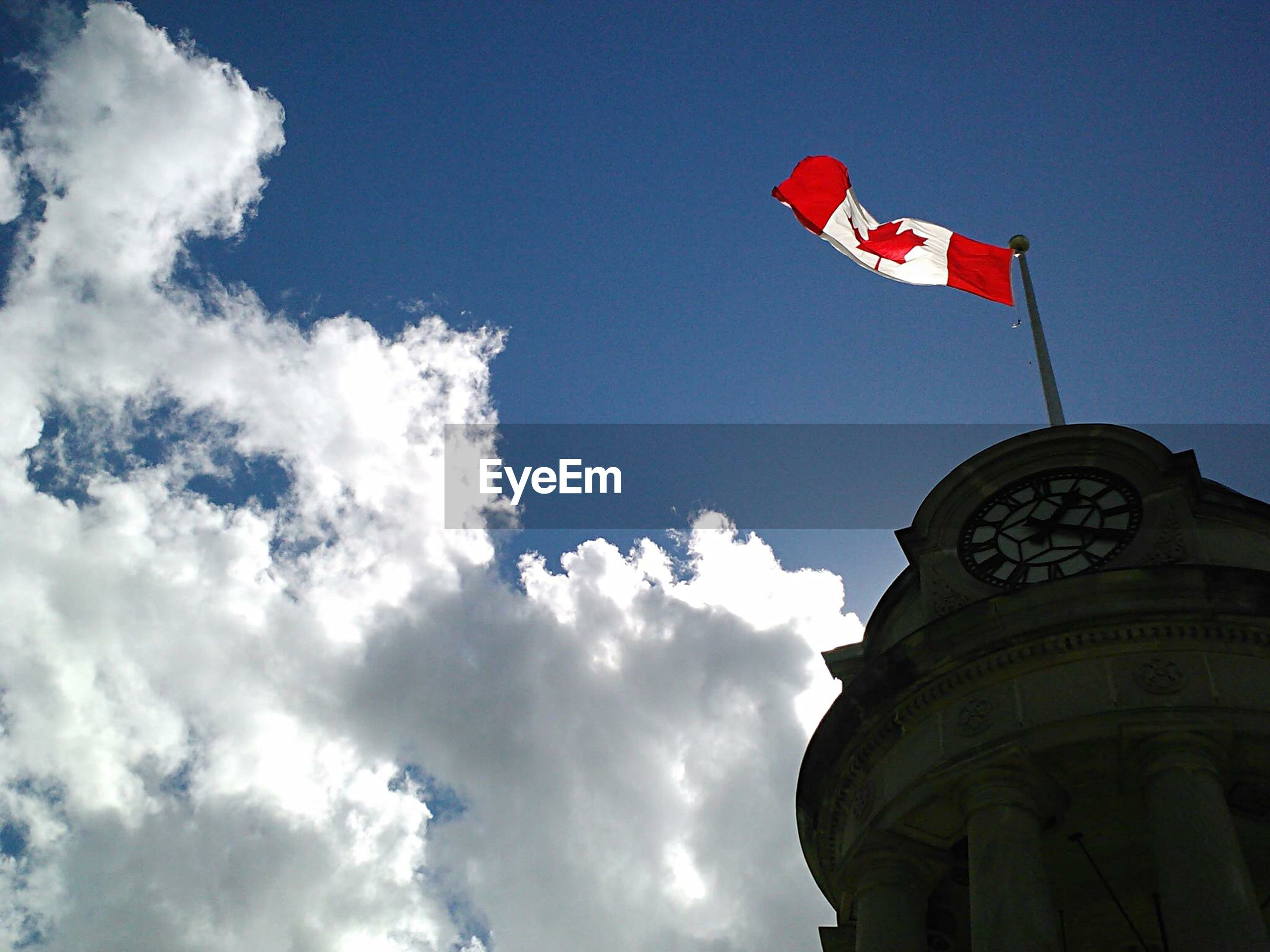 Low angle view of canadian flag on historic building against sky