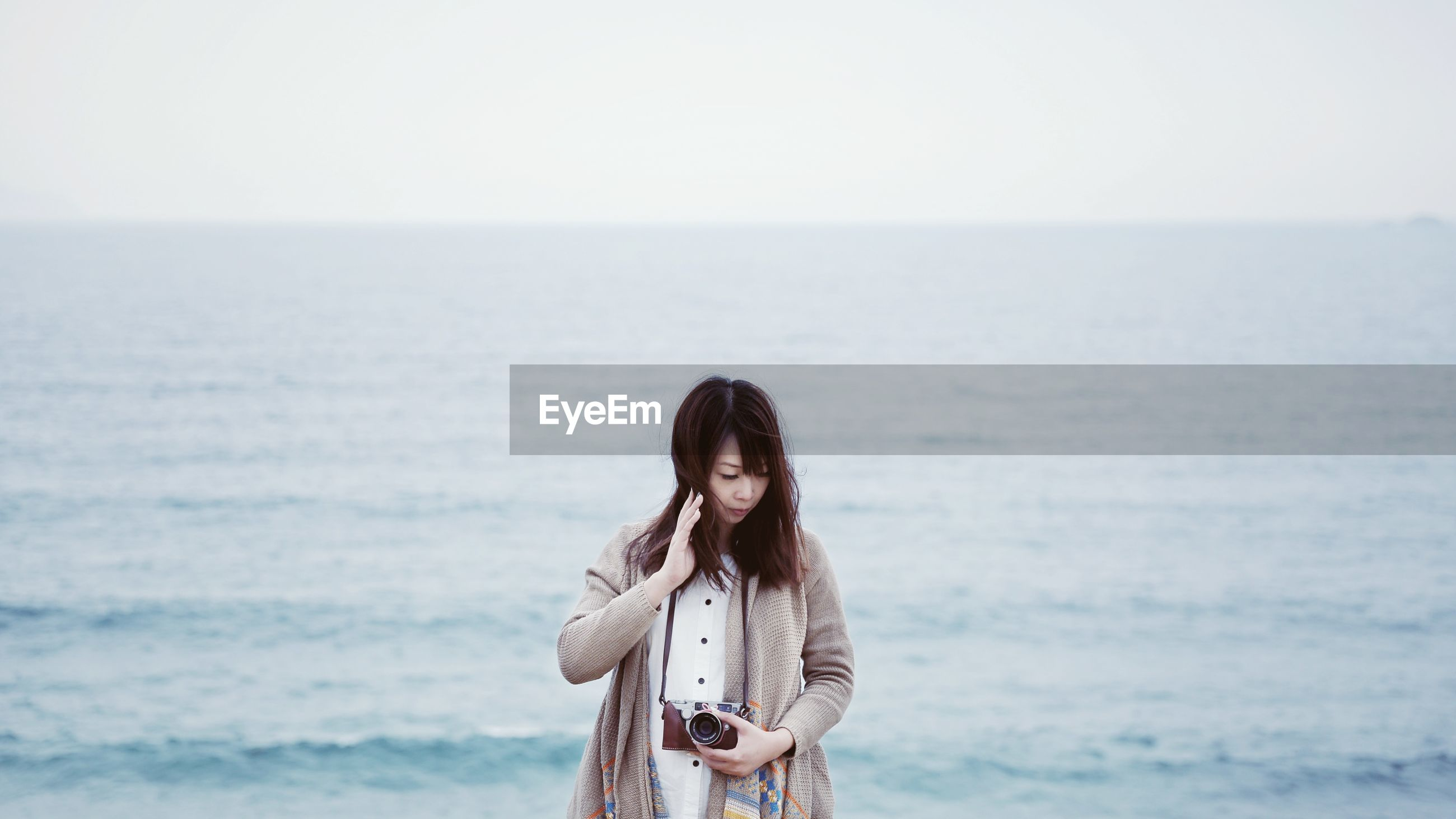Woman looking down while holding camera against sea at beach