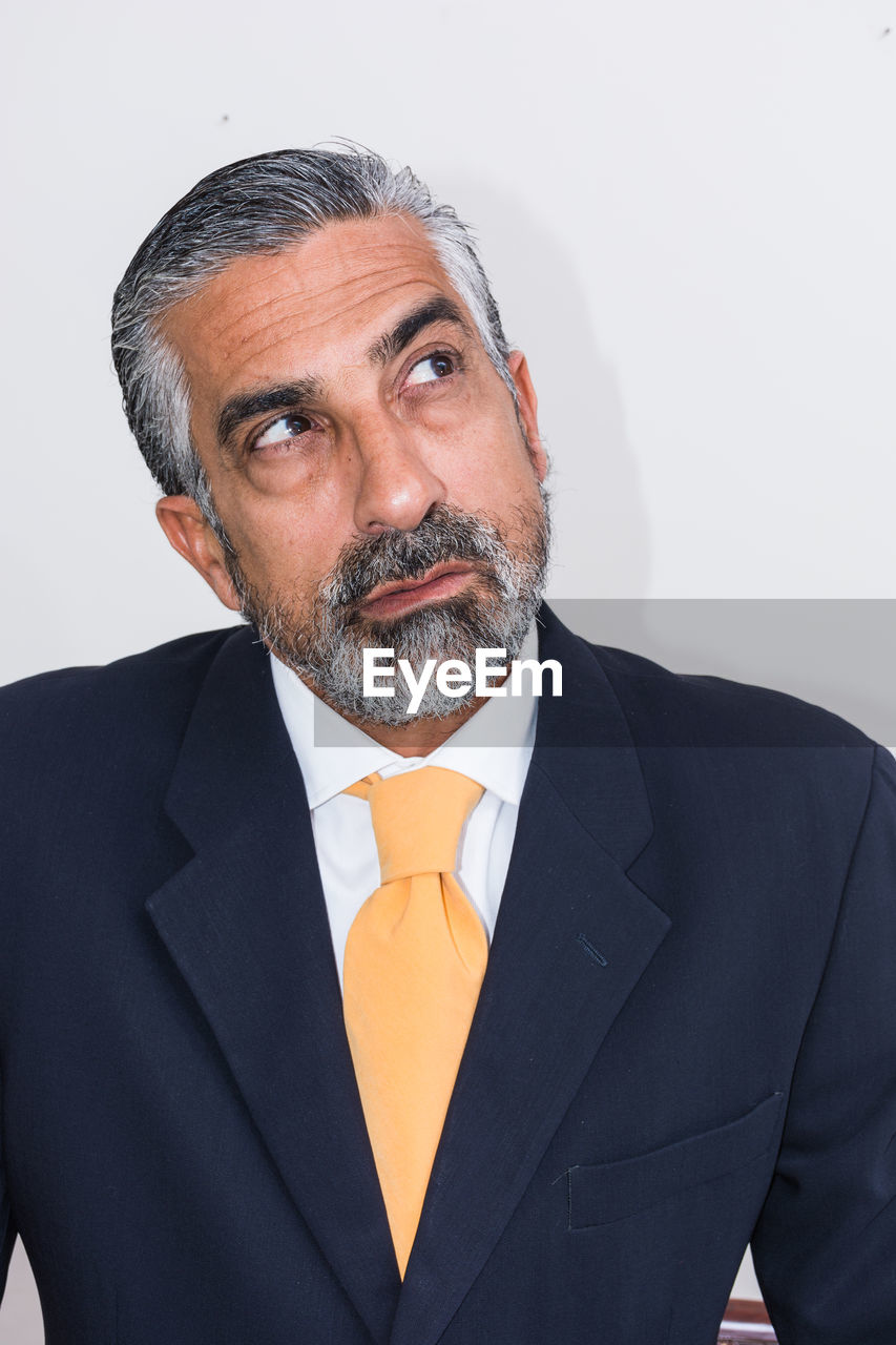 Close-up of mature businessman looking away against wall