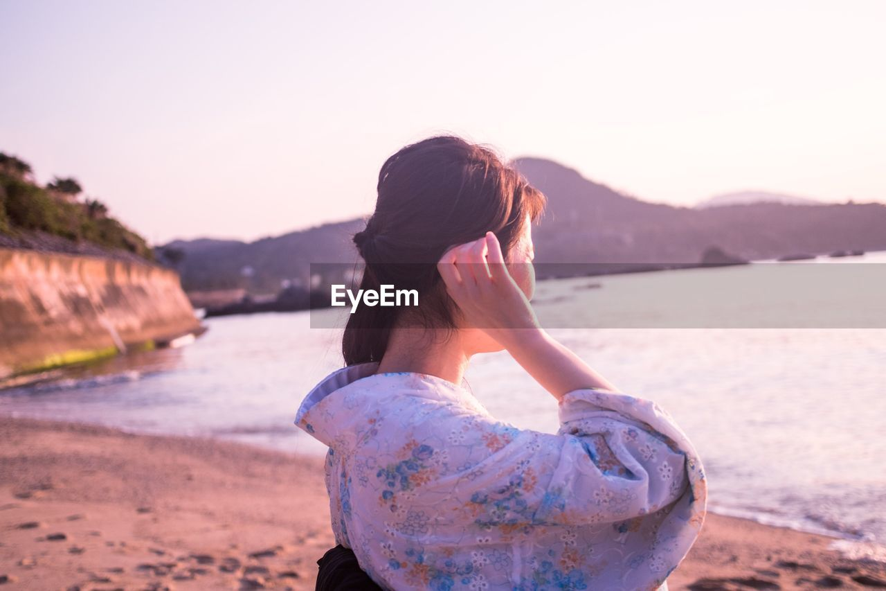 Young Woman Standing At Beach Against Clear Sky