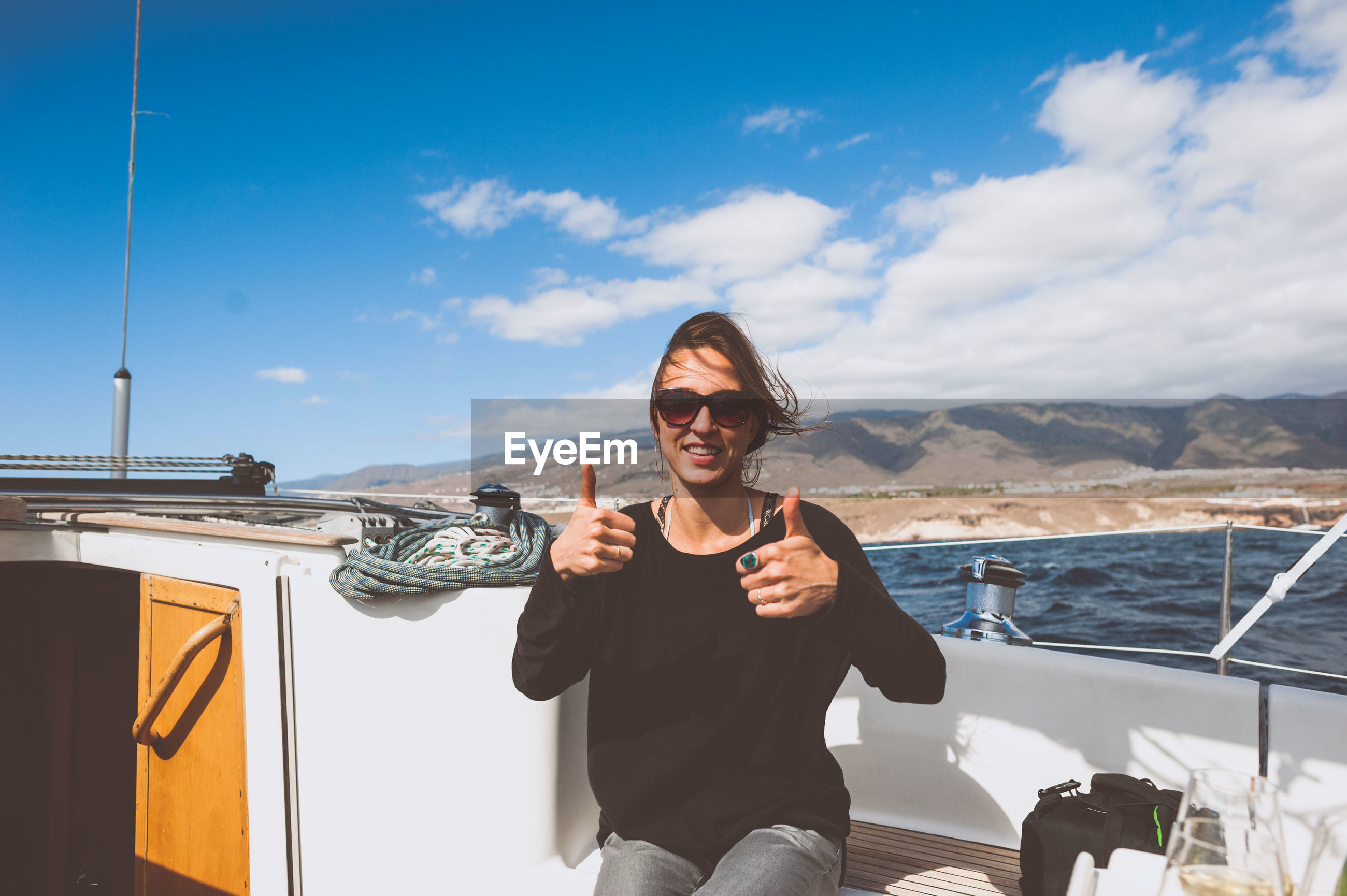 Woman with sunglasses on boat showing thumbs up sign against sky