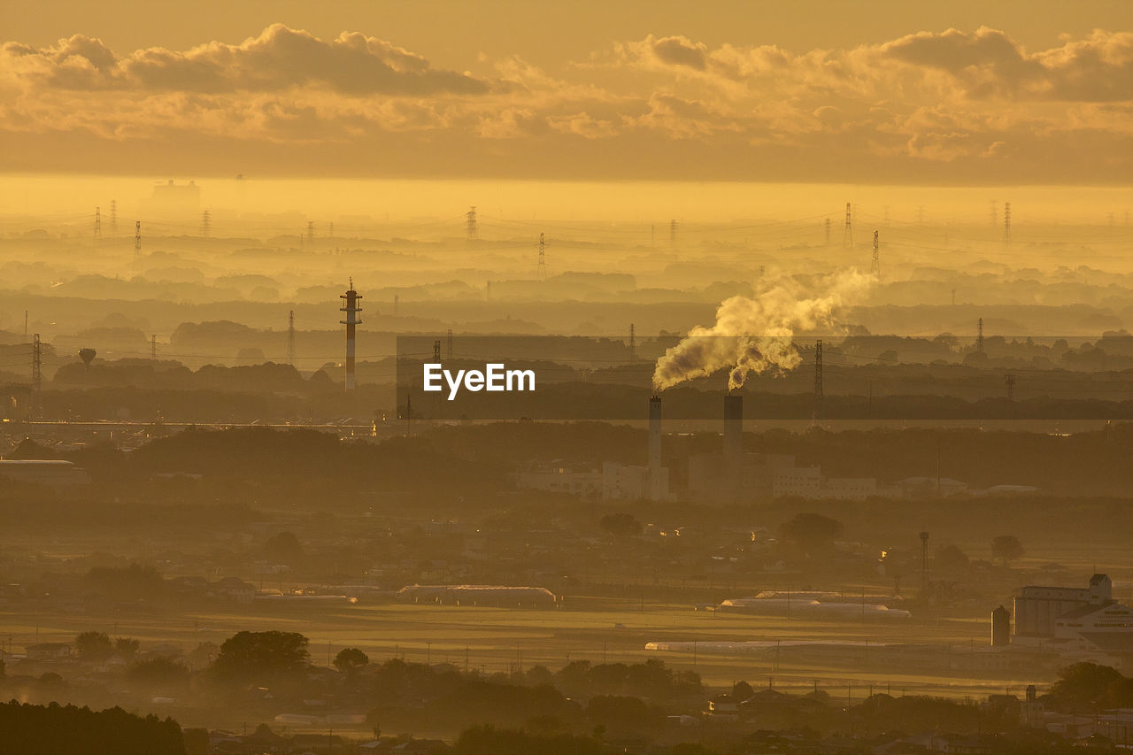 pollution, building exterior, sky, factory, industry, environmental issues, smoke stack, architecture, cloud - sky, built structure, environment, smoke - physical structure, sunset, nature, no people, emitting, air pollution, outdoors, orange color, city, fumes, atmospheric