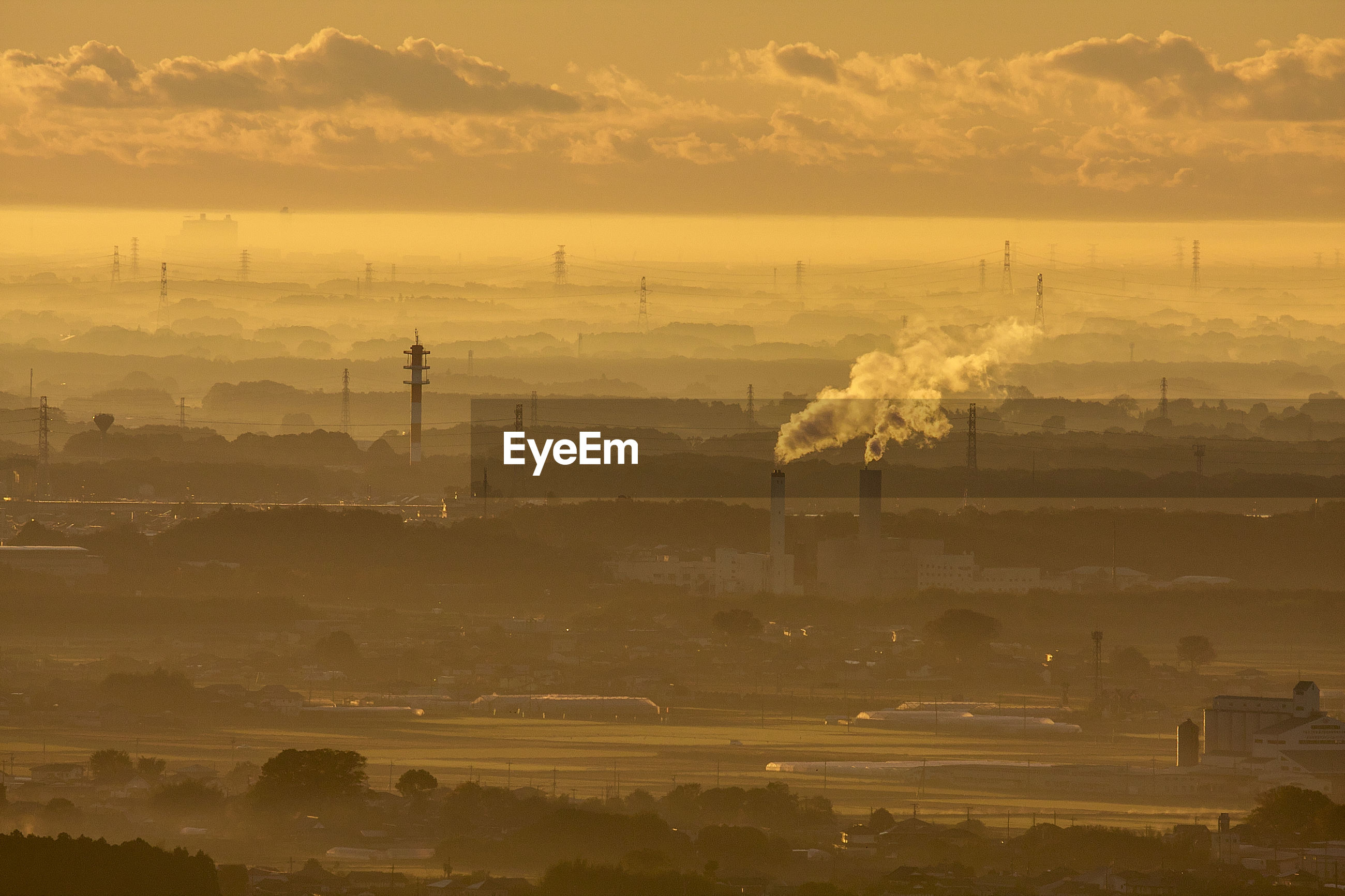 Aerial view of smoke emitting from factory against cloudy sky during sunset