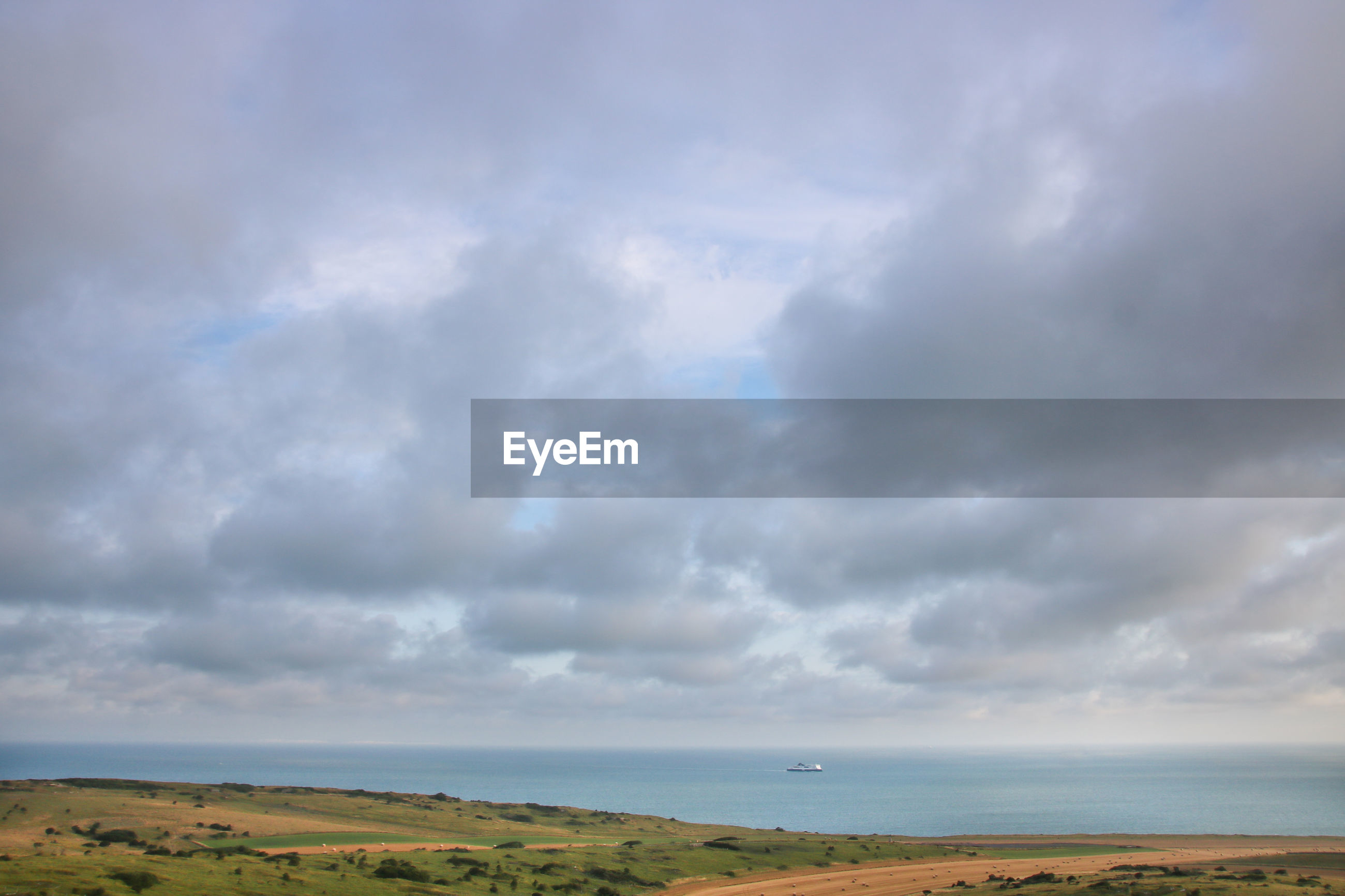 SCENIC VIEW OF LAND AND SEA AGAINST SKY