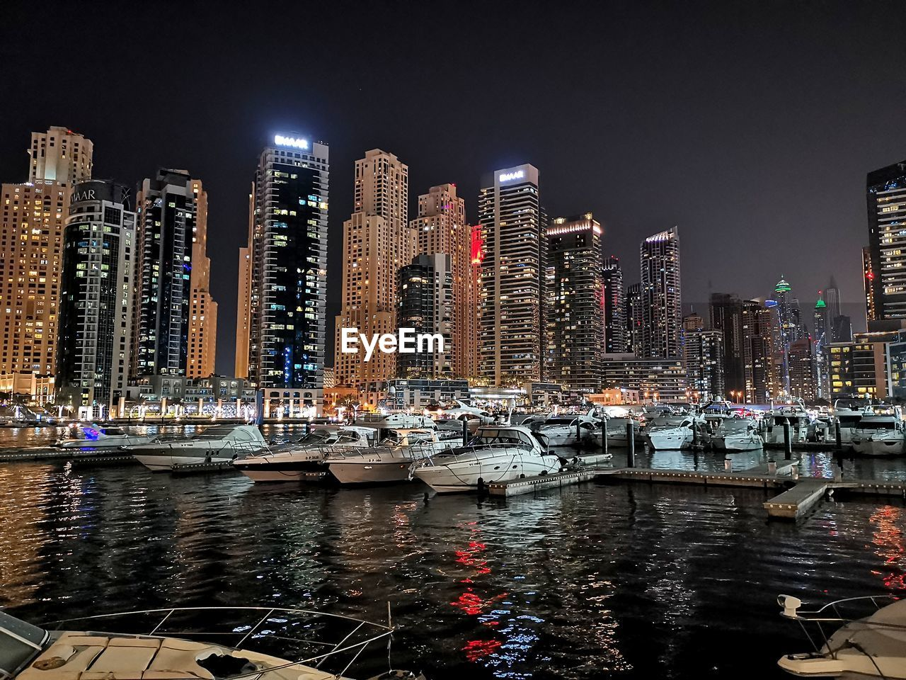 building exterior, architecture, water, built structure, night, city, nautical vessel, illuminated, transportation, building, mode of transportation, sky, waterfront, no people, office building exterior, tall - high, nature, skyscraper, cityscape, modern, outdoors, canal, passenger craft, marina, financial district, yacht