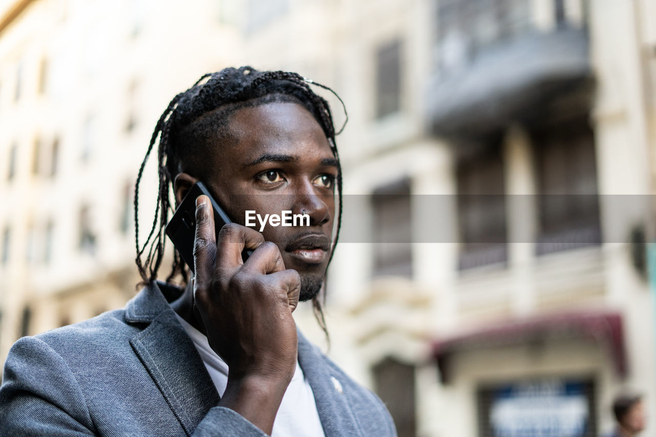 Close-up of young man talking on mobile phone in city