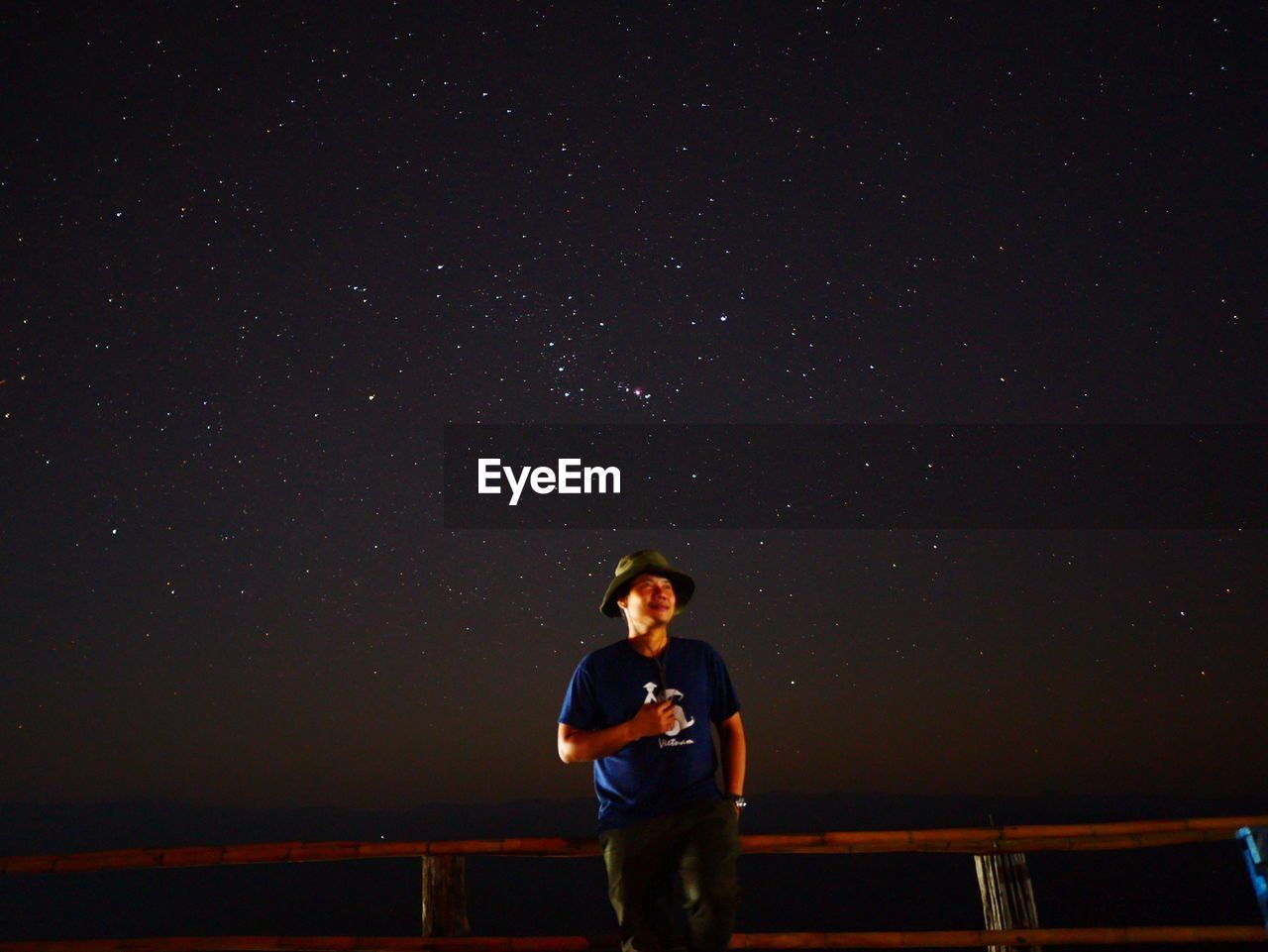 Full length of young man standing against sky at night