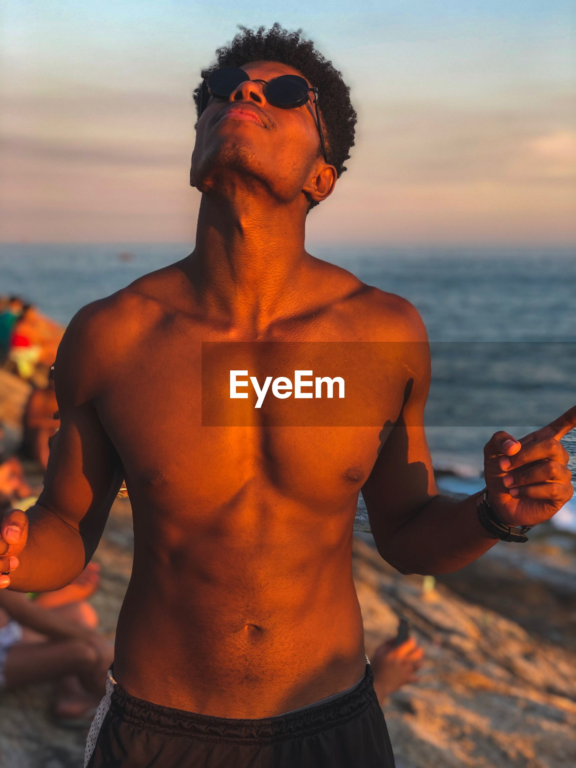 Shirtless young man standing at beach during sunset
