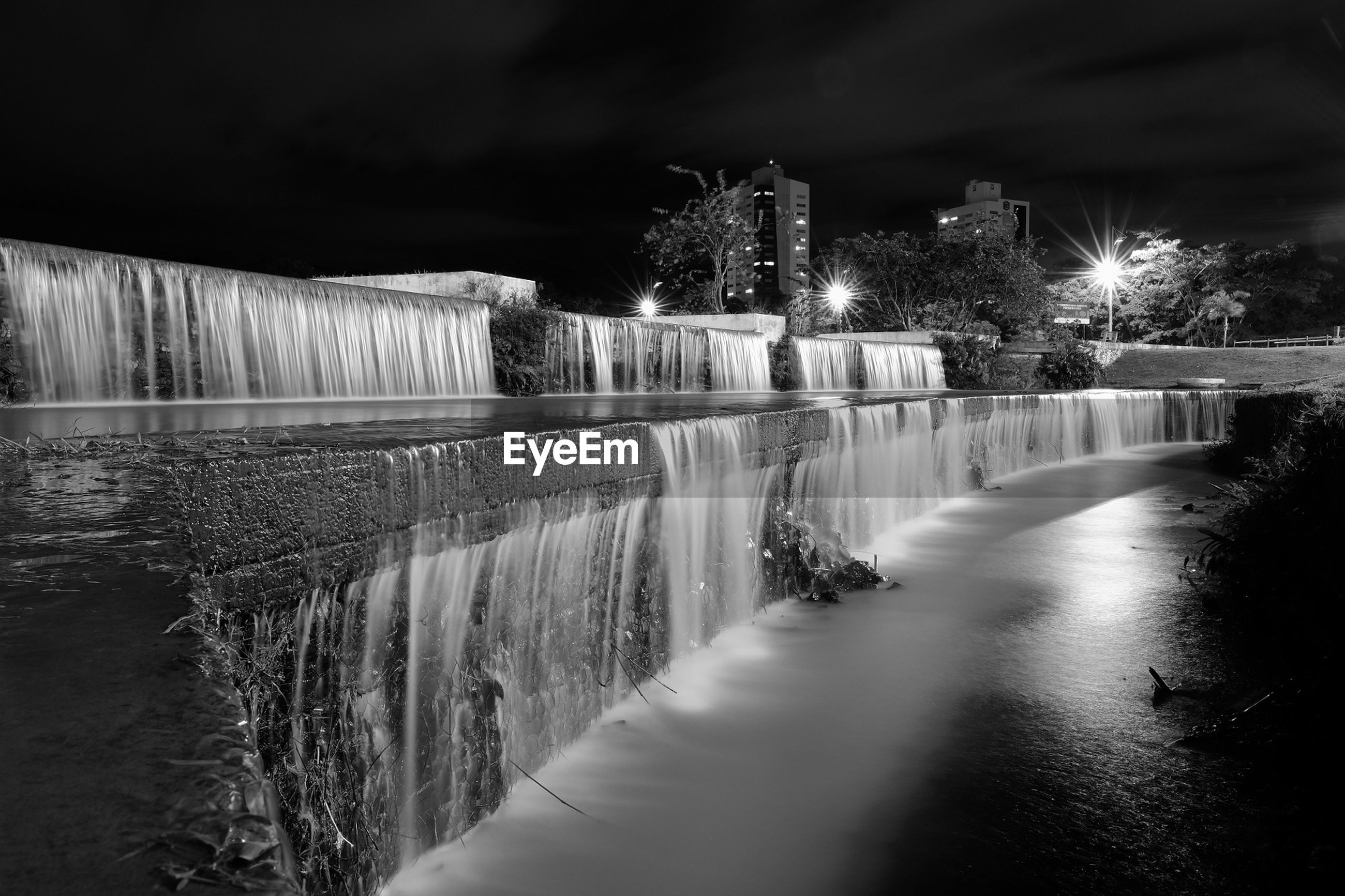 Blurred motion of waterfall in illuminated city at night