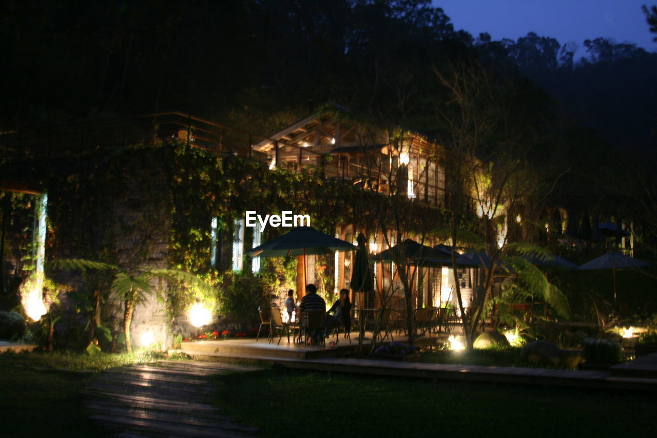 night, illuminated, architecture, tree, built structure, outdoors, real people, building exterior, water, swimming pool, sky, nature