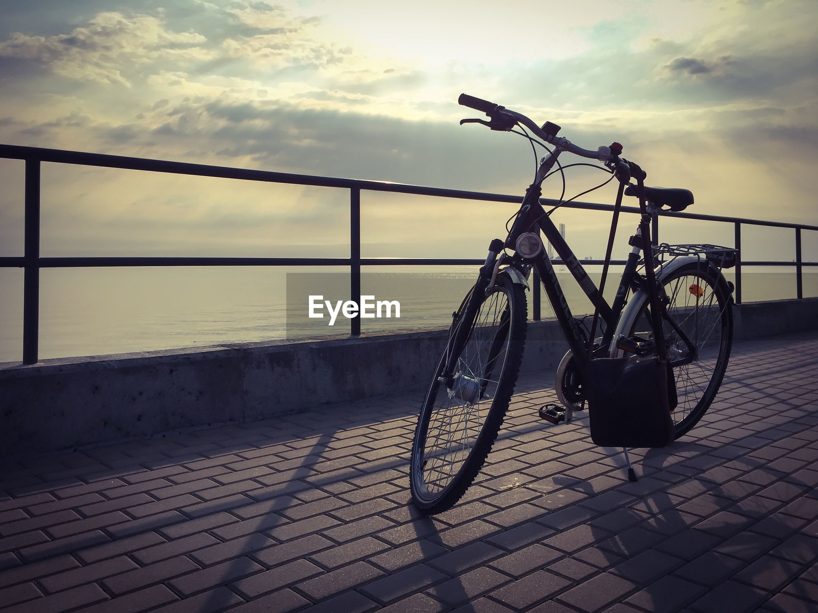 Bicycle parked by railing at seaside