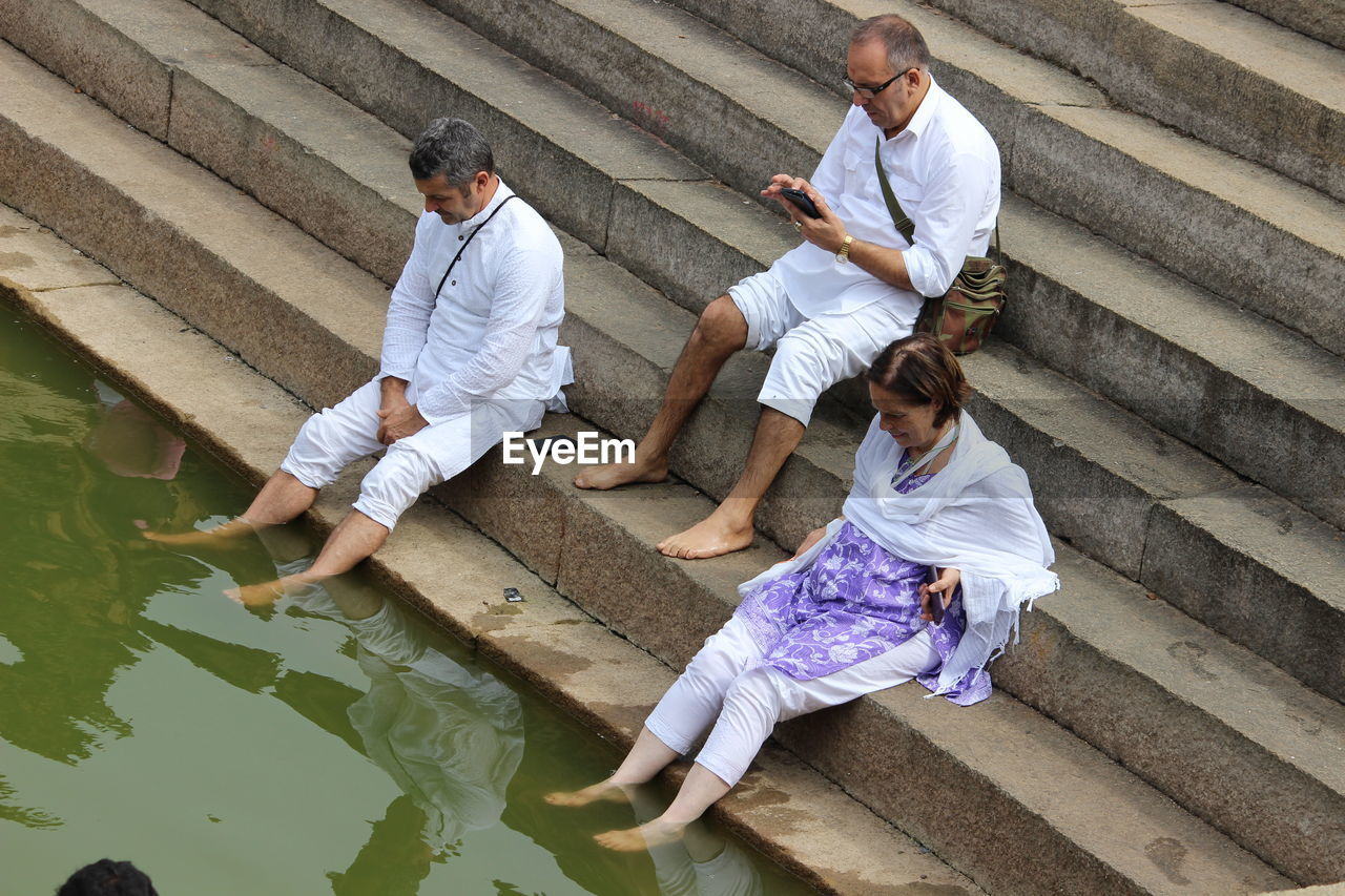 People Sitting On Steps At Riverbank