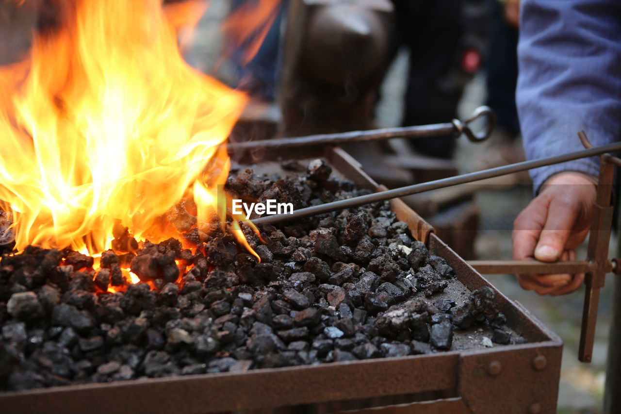 burning, fire, fire - natural phenomenon, flame, heat - temperature, real people, food and drink, food, human hand, hand, nature, barbecue, meat, unrecognizable person, preparation, wood - material, human body part, day, barbecue grill, one person, preparing food, outdoors, bonfire