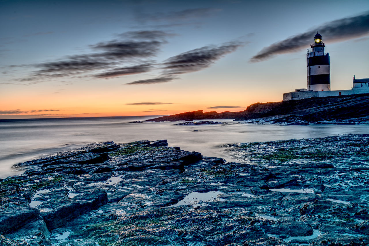 sunset, sea, lighthouse, architecture, sky, cloud - sky, building exterior, built structure, guidance, water, nature, scenics, beauty in nature, no people, beach, outdoors, horizon over water, wave, day
