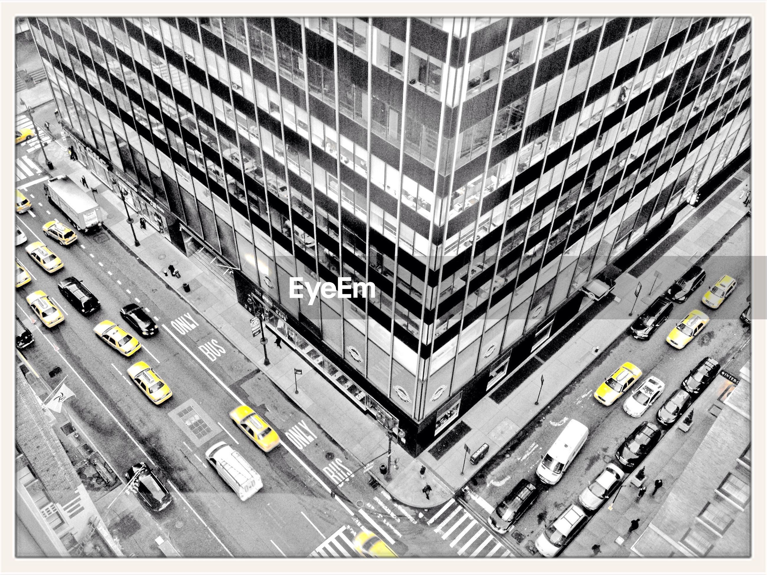 High angle view of cars on city street by glass building