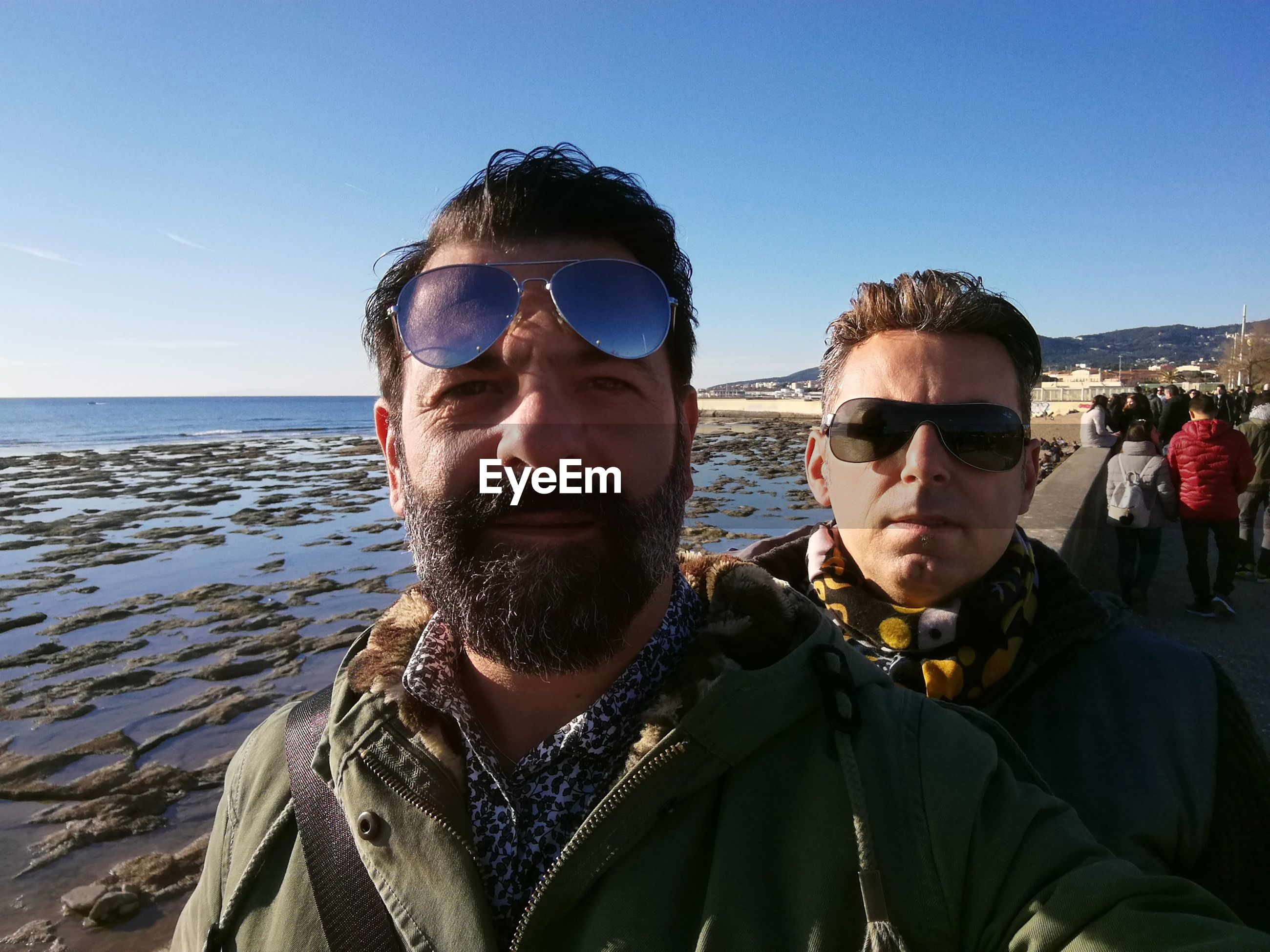 Portrait of friends by sea against sky