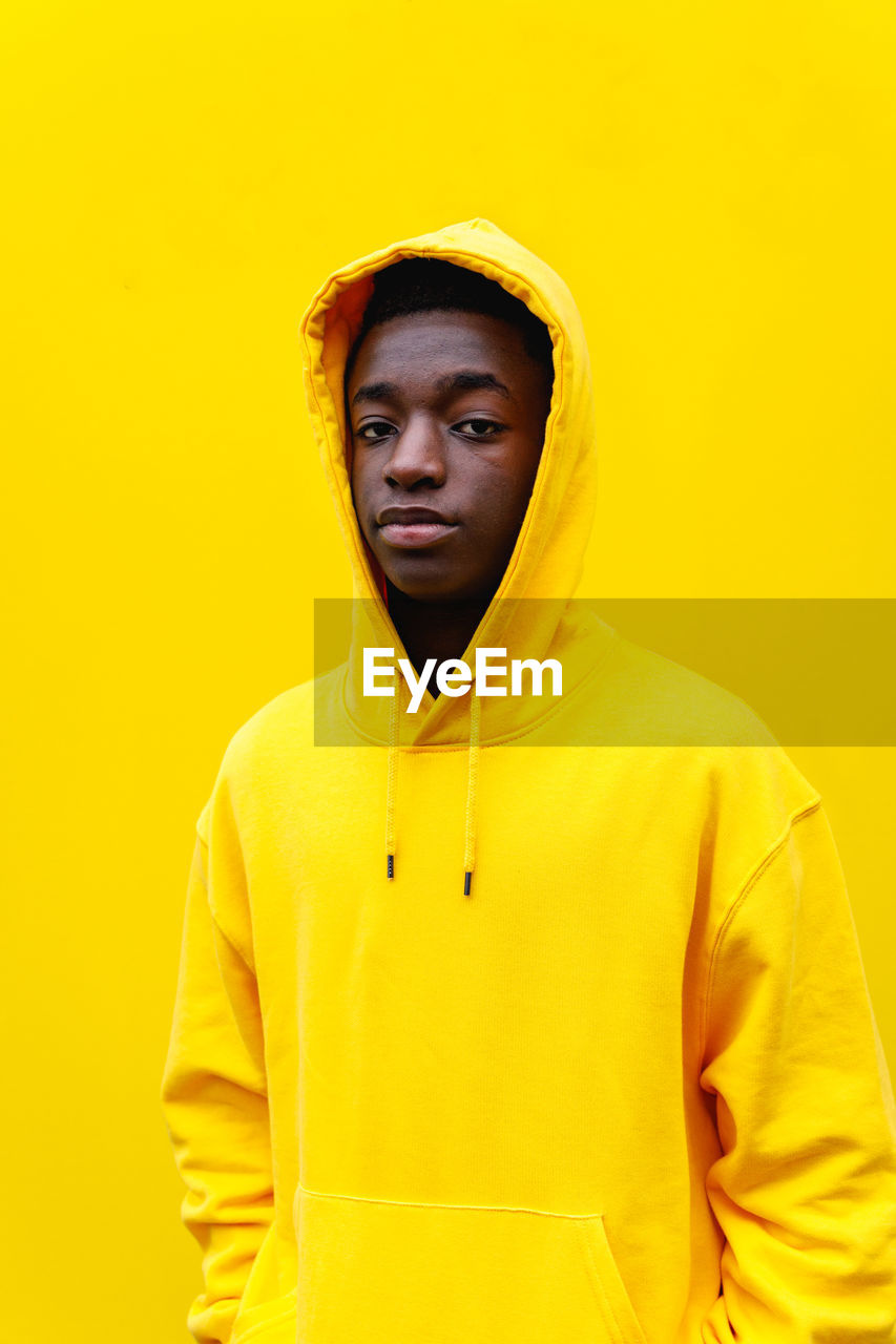 yellow, one person, front view, standing, yellow background, portrait, young adult, waist up, studio shot, young men, clothing, casual clothing, colored background, looking at camera, lifestyles, indoors, real people, hood, hood - clothing