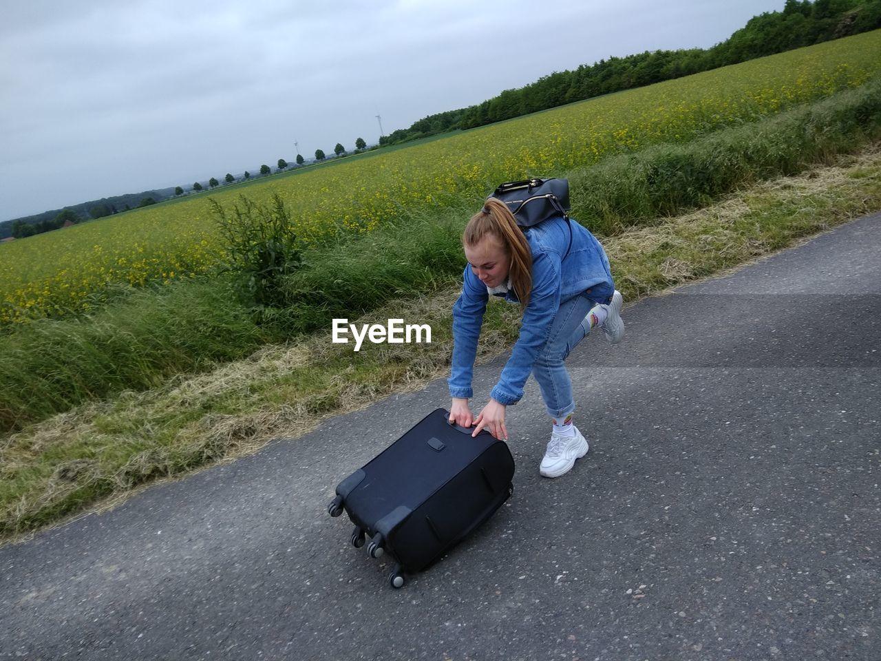 High angle view of teenage girl pushing luggage on road