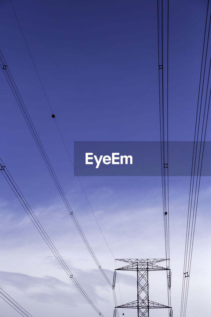 cable, sky, connection, electricity, low angle view, power supply, power line, technology, fuel and power generation, no people, electricity pylon, nature, metal, cloud - sky, outdoors, built structure, architecture, blue, complexity, transportation, electrical equipment